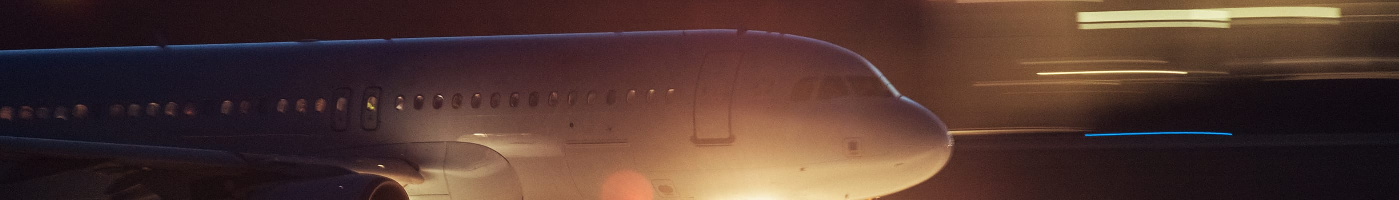 Image of passenger jet moving from left to right, with lights zooming past.